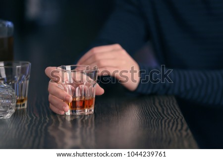 Woman with glass of drink in bar, closeup. Alcoholism problem