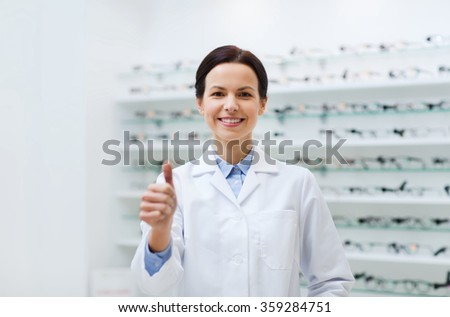 woman with glasses and thumbs up at optics store - stock photo
