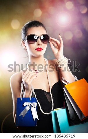 Woman with glasses  holding shopping bags against a black background.Style beauty girl with shopping bags.Portrait of stunning young woman in sunglasses carrying multicolored shopping bags . - stock photo