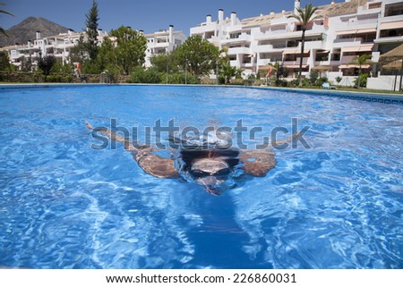 woman with goggles diving breaststroke in a blue pool - stock photo