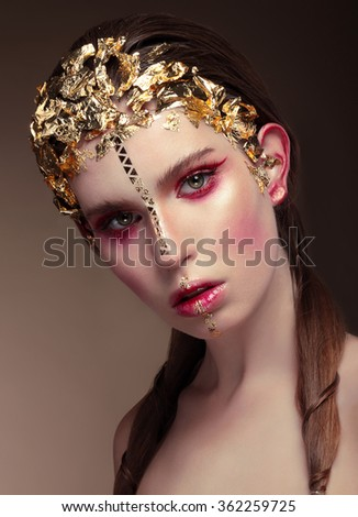 Woman with gold face make up fashion on brown background.