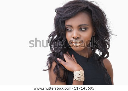 Woman with gold lips wearing black dress on whtie background