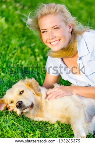 Woman with golden retriever lying on the green grass in the park