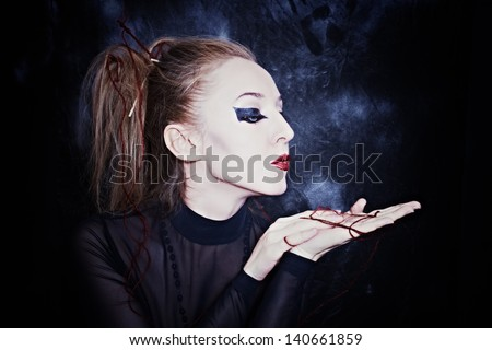Woman with gothic style makeup on a black background - stock photo