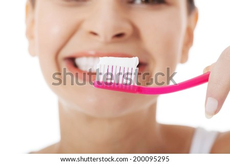 Woman with great teeth holding tooth brush - stock photo