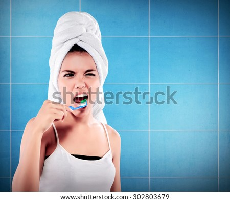Woman with great teeth holding tooth-brush on bathroom background - stock photo