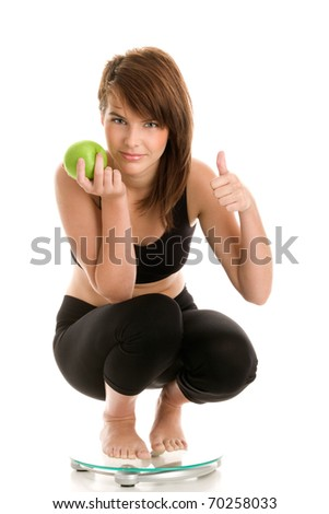 Woman with green apple crouching on scale - stock photo