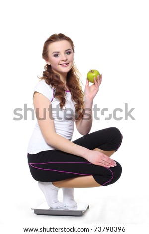 Woman with green apple on scale - stock photo