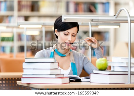 Woman with green apple surrounded with piles of books reads sitting at the desk at the library. Academic achievement - stock photo