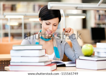 Woman with green apple surrounded with piles of books reads sitting at the table at the library. Knowledge is power