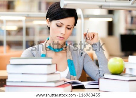 Woman with green apple surrounded with piles of books reads sitting at the table at the library. Educational process - stock photo