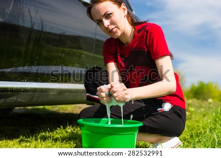 Woman with Green Bucket Wringing Out Soapy Sponge and Washing Black Luxury Vehicle in Green Field on Bright Sunny Day with Blue Sky