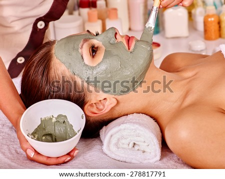Woman with green clay facial mask in beauty spa. - stock photo