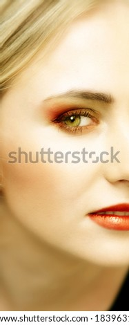 Woman with green eyes and striking bright make-up - stock photo