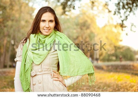 woman with green scarf in in autumn park