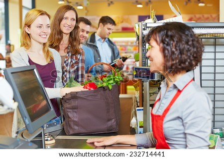 Woman with groceries waiting in line at the supermarket checkout - stock photo
