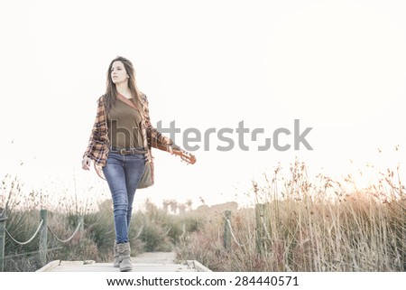 Woman with guitar on a catwalk in the field enjoying nature - stock photo
