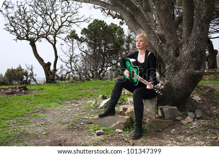 woman with guitar under tree - stock photo