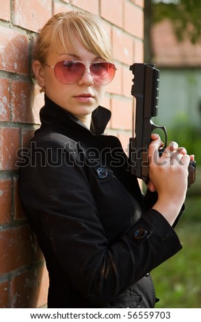 woman with gun against  the brick wall - stock photo