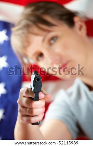 Woman with gun aiming at something, US flag in background - stock photo