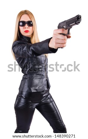 Woman with gun in black leather costume - stock photo