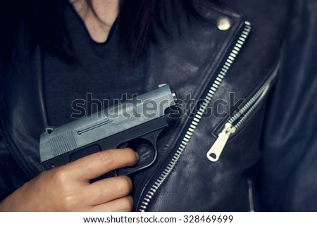 Woman with gun in hand on the black jacket texture background - stock photo
