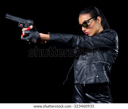 Woman with gun isolated on black - stock photo