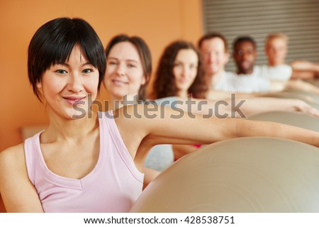 Woman with gym ball in pilates class at fitness studio - stock photo