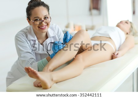 Woman with hair removal beauty clinic on foot - stock photo