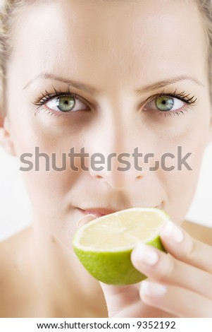 woman with half fresh lime, skin retouched - stock photo