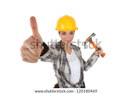 Woman with hammer giving thumbs up. - stock photo