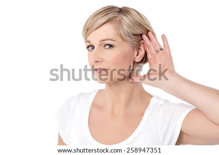 Woman with hand behind her ear and listens carefully - stock photo