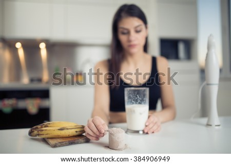 Woman with hand blender making sweet banana chocolate protein powder milkshake smoothie.Drinking protein after workout.Whey,banana and low fat milk sport nutrition diet after gym.Healthy lifestyle - stock photo