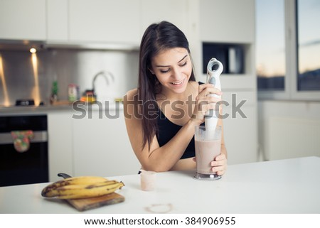 Woman with hand blender making sweet banana chocolate protein powder milkshake smoothie.Drinking protein shake after workout.Whey,banana,low fat milk sport nutrition diet after gym.Healthy lifestyle - stock photo