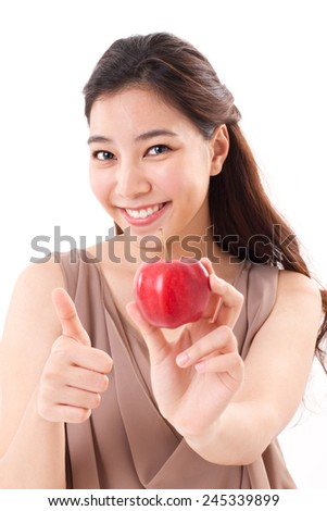 woman with hand holding red apple, giving thumb up hand gesture - stock photo