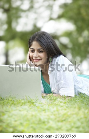 Woman with hand on chin looking at laptop screen and smiling