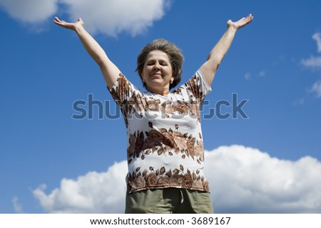 woman with hand up on blue sky and clouds