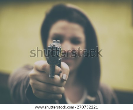 Woman with handgun. Analog effected photo - stock photo