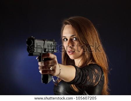 Woman with handgun on blue background - stock photo