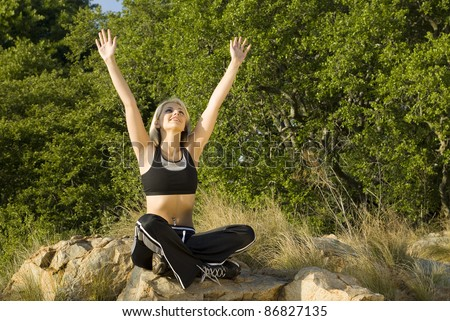 Woman with hands above head in praise in park - stock photo