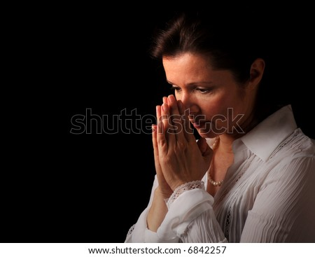 Woman with hands folded in prayer and contemplation - stock photo