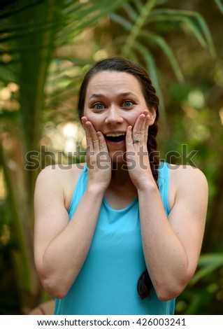 Woman with hands on her face with surprised look - stock photo