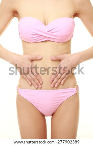 Woman with hands over belly - stock photo