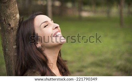 Woman with happy expression relaxing on meadow - stock photo