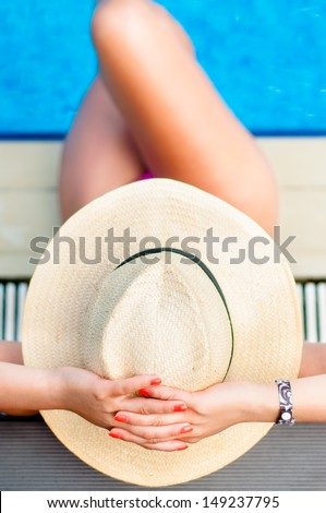 Woman with hat relaxing at the inside pool at beach resort