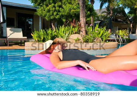 Woman with hat relaxing in outdoor swimming pool on air mattress