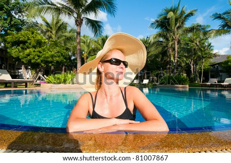 Woman with hat relaxing in swimming pool - stock photo