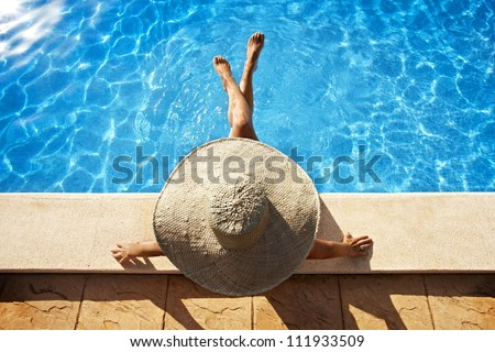 Woman with hat sitting at poolside