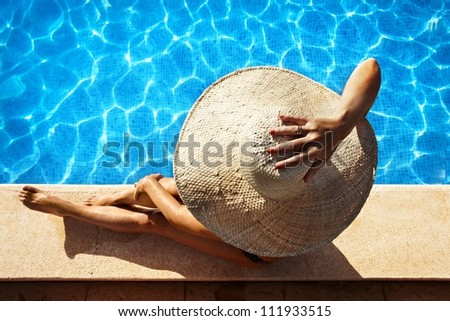 Woman with hat sitting at poolside - stock photo