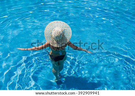 Woman with hat  standing in the swimming pool - stock photo
